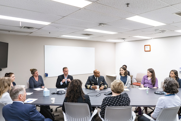 Geography Graduate Student Emma Gause, U.S. Surgeon General Dr. Jerome Adams, and others sitting around a conference table.