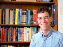 Photo of Sam Kay in front of bookshelf full of books