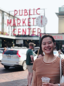 Geography Alum Utako Kase Stands at the Entrance to Pike Place Market