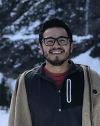 photo of Edgar smiling with mountain background