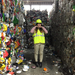 A geography intern standing in the middle of recycled materials.