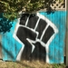 Raised fist, a universal symbol of solidarity and support. Artist Dave Savage.